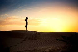 Silhouette of a woman standing alone on a desert sand dune against a sunset