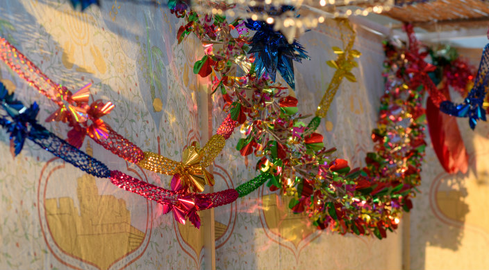 Shiny, colorful decorations strung in a sukkah