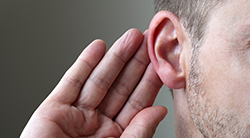 a man cups his ear to listen