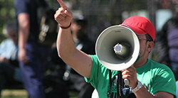 Man with a megaphone shouts in protest, like Korach