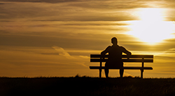 A man on a bench contemplates the sunset