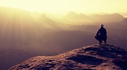 Man views a mountain sunset