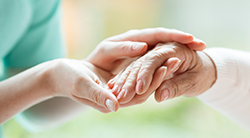 A woman holds a senior's hand