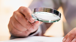 A man examines a document with a magnifying glass