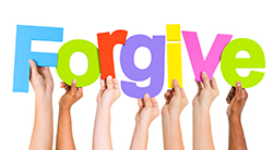 Many hands hold up a sign saying Forgive