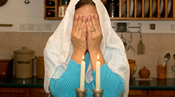 A woman covers her face with her hands to recite the Shabbat blessing over candles