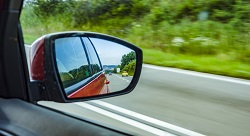 view of the road from a car's side-view mirror