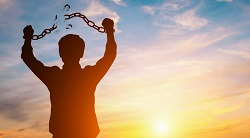 A man raises his hands showing a broken chain