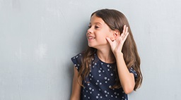 Young girl cups her ear to listen
