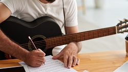a person with a guitar writes music