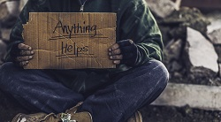 a man hold a sign asking for help