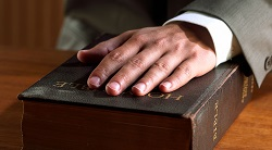 a hand rests on a Bible