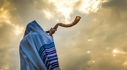 a man wearing a tallit and blowing a shofar outside