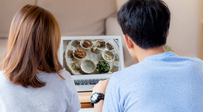 Two people with their backs to the camera as they watch a seder on a laptop screen