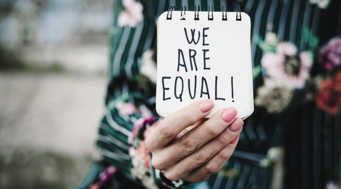 "Woman (from the neck down) holding small notepad that says: ""We Are Equal!"""