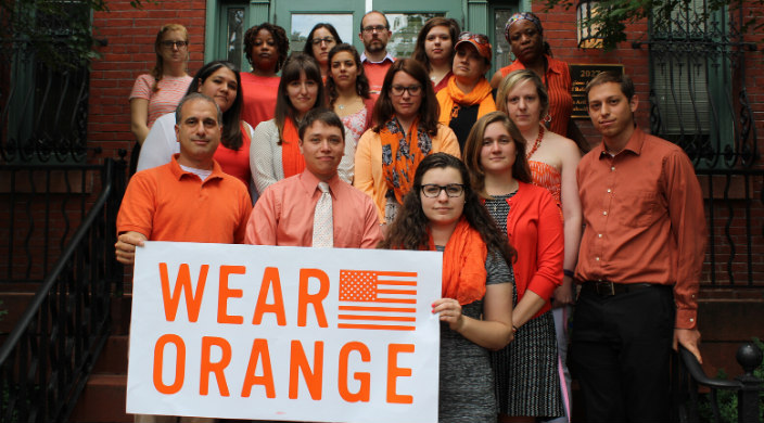 Group of somber people wearing orange clothing and holding a banner that says WEAR ORANGE