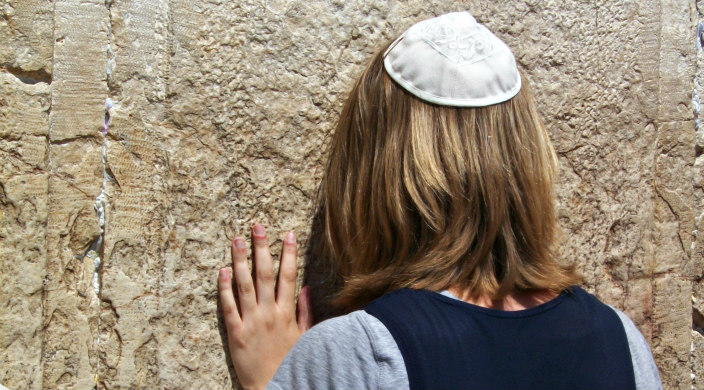 Woman wearing a kippah turned away from the camera with her hand and forehead resting against the Western Wall