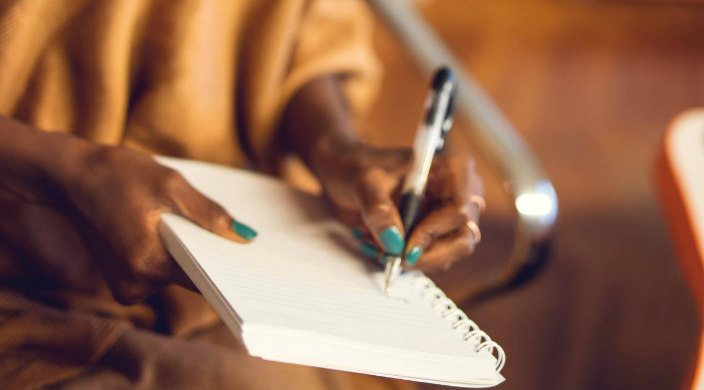 Hand of a Black woman wearing blue nail polish and using a pen to write in a notebook as if penning a letter