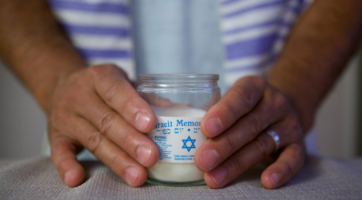 Hands of a person who is wearing a tallit (prayer shawl) holding a yahrzeit candle