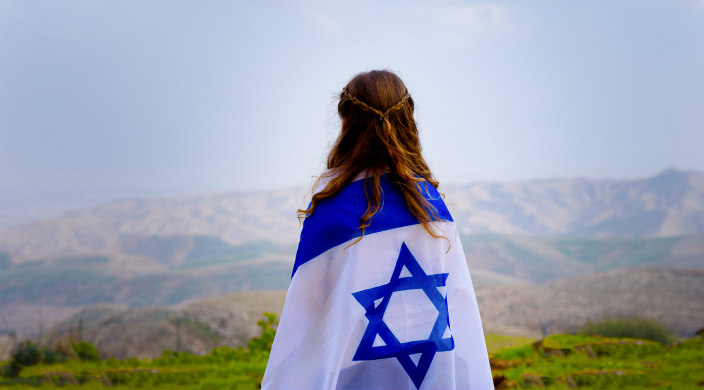 Young woman facing away, wrapped in an Israeli flag